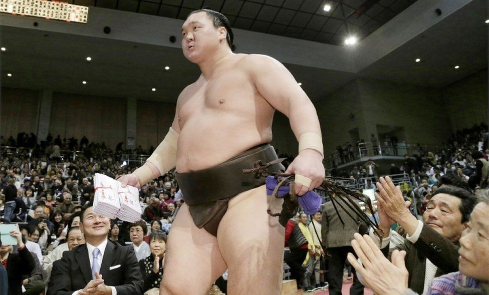 Fans applaud yokozuna-ranked sumo wrestler Hakuho at a tournament on November 25, 2017.