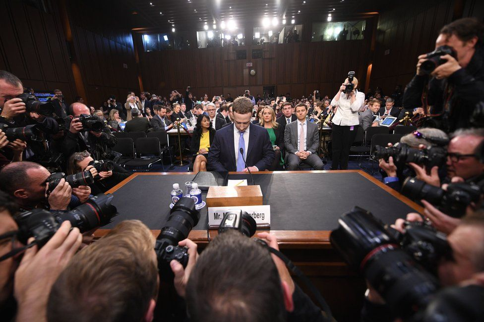 Mark Zuckerberg sits in front of photographers