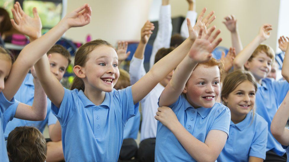 Children putting their hands up to answer questions in a classroom