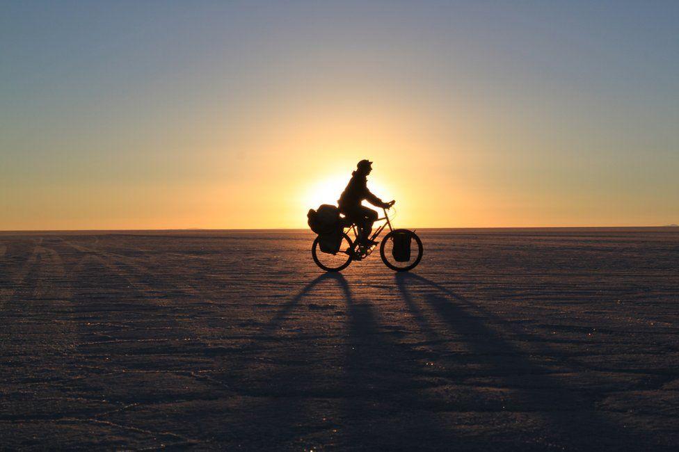 A sunset photo of Stephen cycling through a salt flat