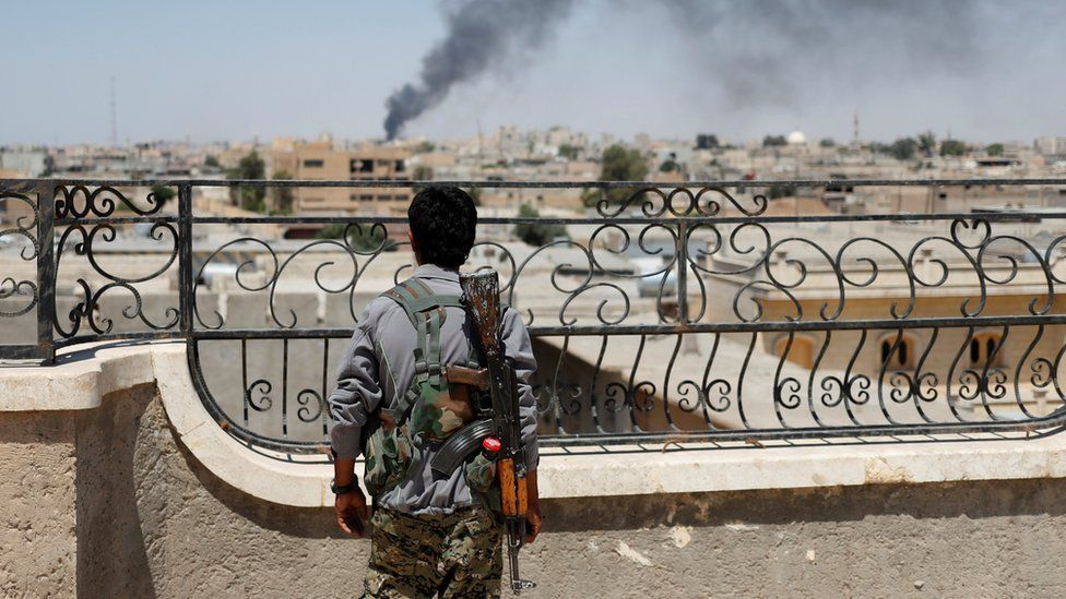 A Kurdish fighter looks across Raqqa after a coalition airstrike