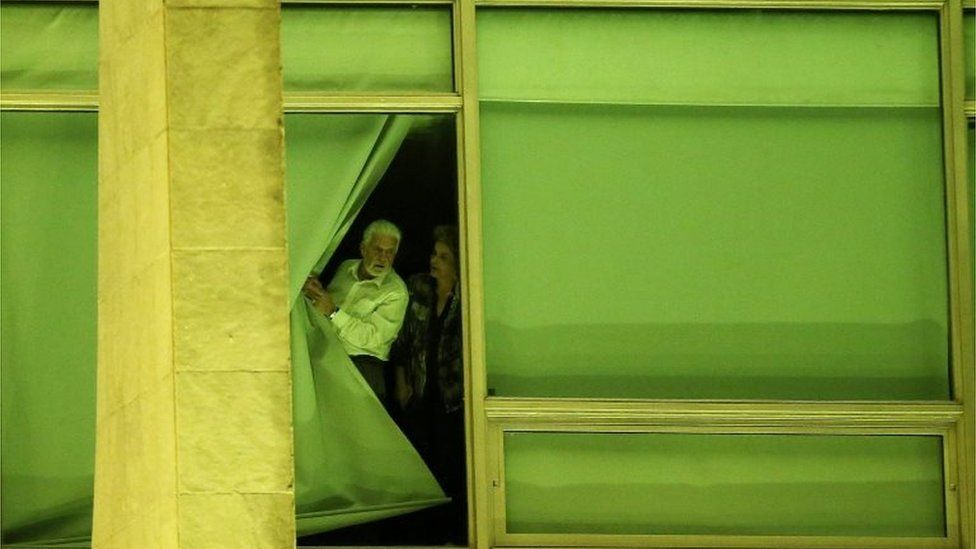 Brazil's President Dilma Rousseff, accompanied by Chief of Staff Jaques Wagner, looks from a window at Planalto Palace in Brasilia, Brazil, May 11, 2016
