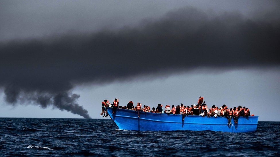 Migrants wait to be rescued as they drift at sunset in the Mediterranean Sea some 20 nautical miles north off the coast of Libya on October 3, 2016.
