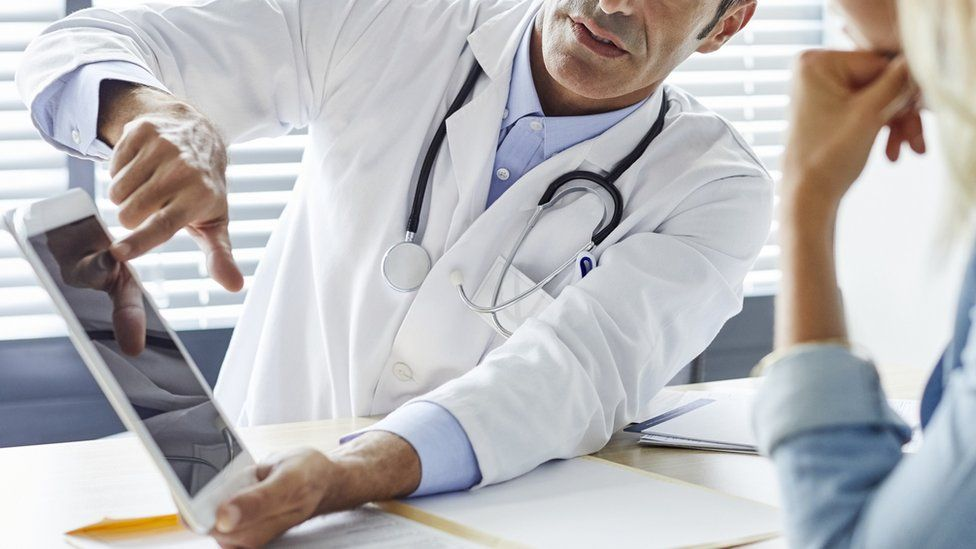 A doctor shows information to a patient on a tablet computer