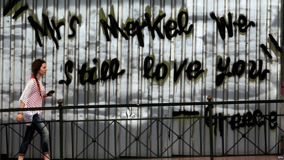 "A woman walks in front of a graffito in Athens reading ""Mrs Merkel we still love you"", 27 June"