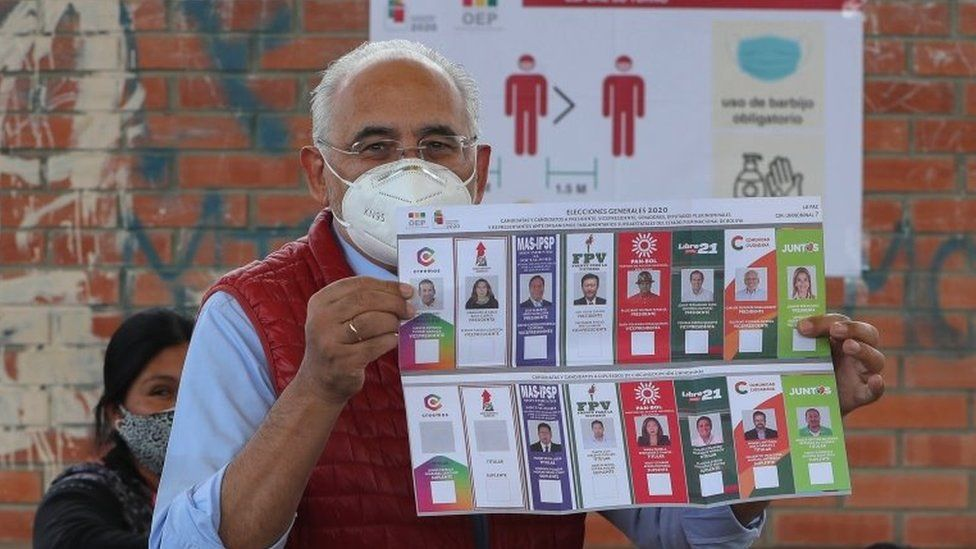 Presidential candidate Carlos Mesa shows the electoral ballot when casting his vote in a precinct in the city of La Paz, Bolivia, 18 October 2020.