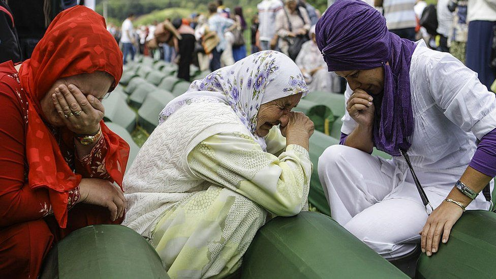 Bosnian Muslim women cry over the coffins of those murdered at Srebrenica