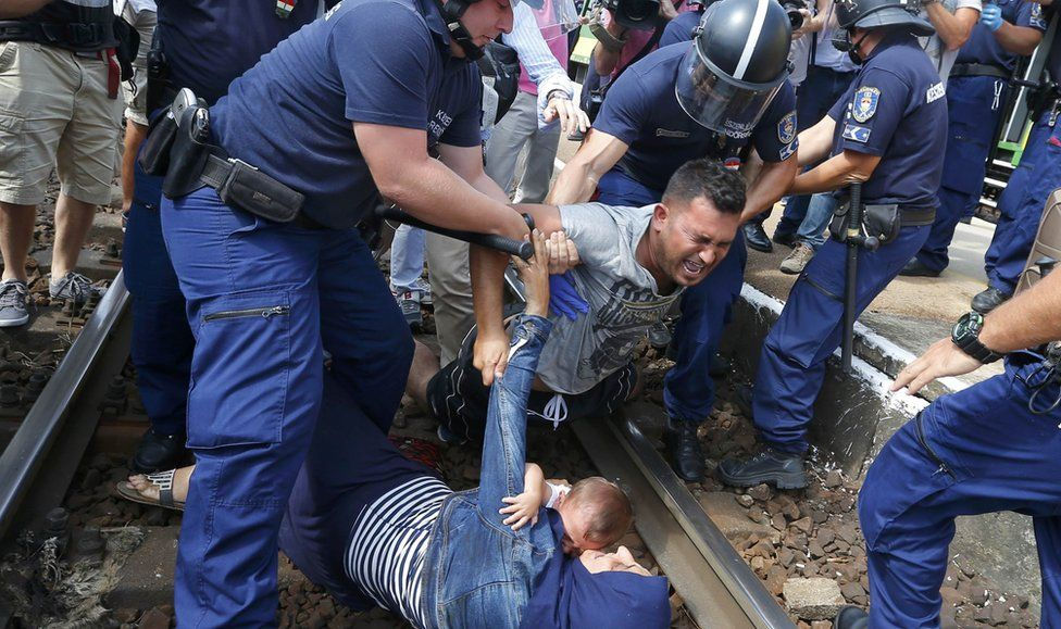 Hungarian policemen detain migrants on the tracks as they wanted to run away at the railway station in the town of Bicske, Hungary, 3 September 2015