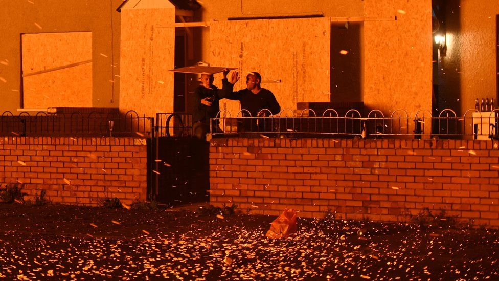 Two men take shelter from embers blowing from a bonfire at Hopewell Square in Belfast's Shankill area