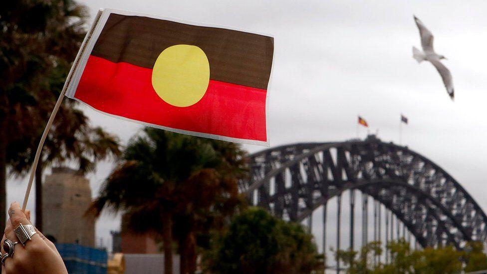 An Aboriginal flag in front of the Sydney Harbour Bridge