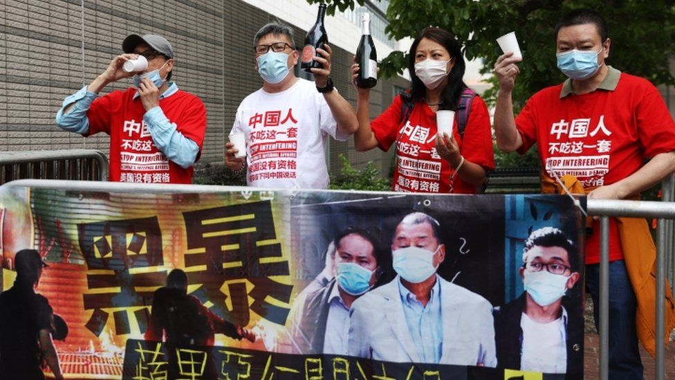 Pro-Beijing demonstrators celebrate the sentences