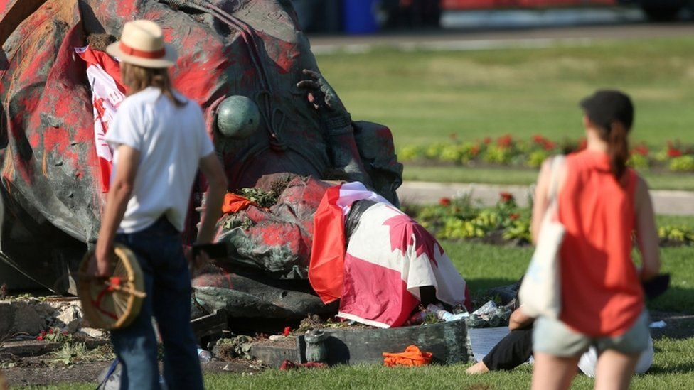 A statue of Queen Victoria lies upended on the floor
