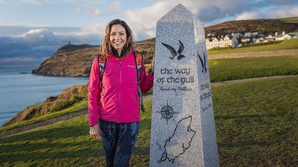Julia Bradbury next to a granite marker