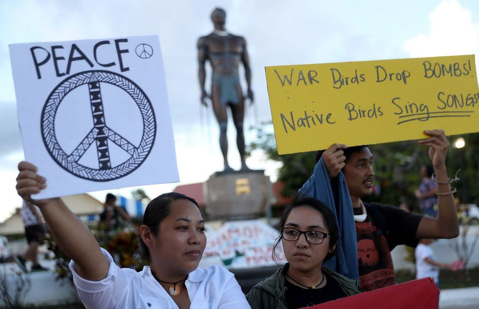 Protesters hold signs during a People for Peace Rally at the Chief Quipuha Statue on 14 August 2017 in Hagatna, Guam.