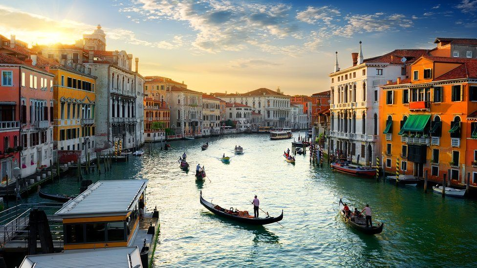 A few boats slip through the broad expanse of the Venice Grand canal in golden late evening light