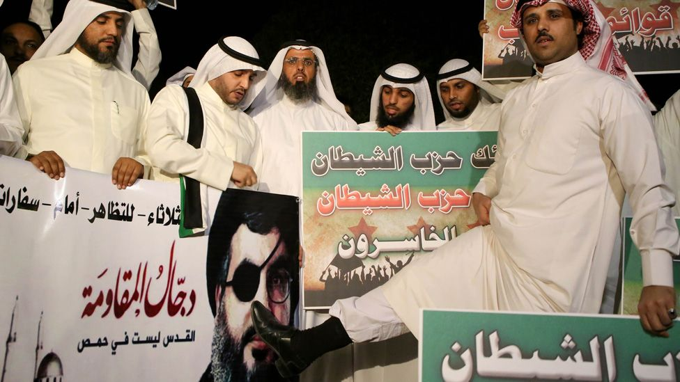 Kuwaiti protesters hold placards against Lebanese Shiite movement Hezbollah's chief Hassan Nasrallah (portrait) during a protest in front the Lebanese embassy against Hezbollah's and Iran's involvement in Syria, in Kuwait city on June 11,2013.