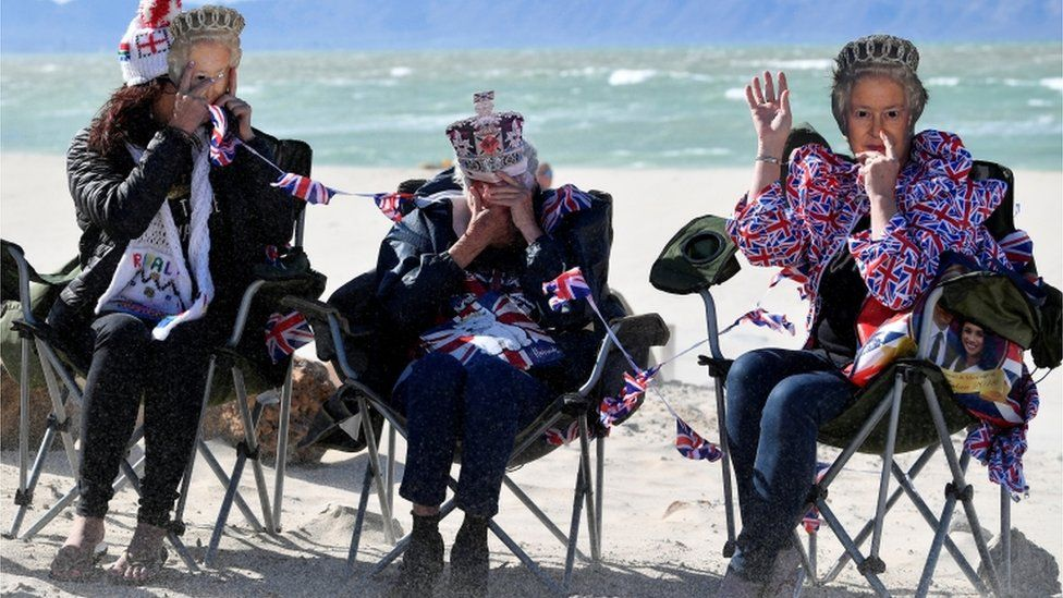 People hold up masks depicting Britain's Queen Elizabeth