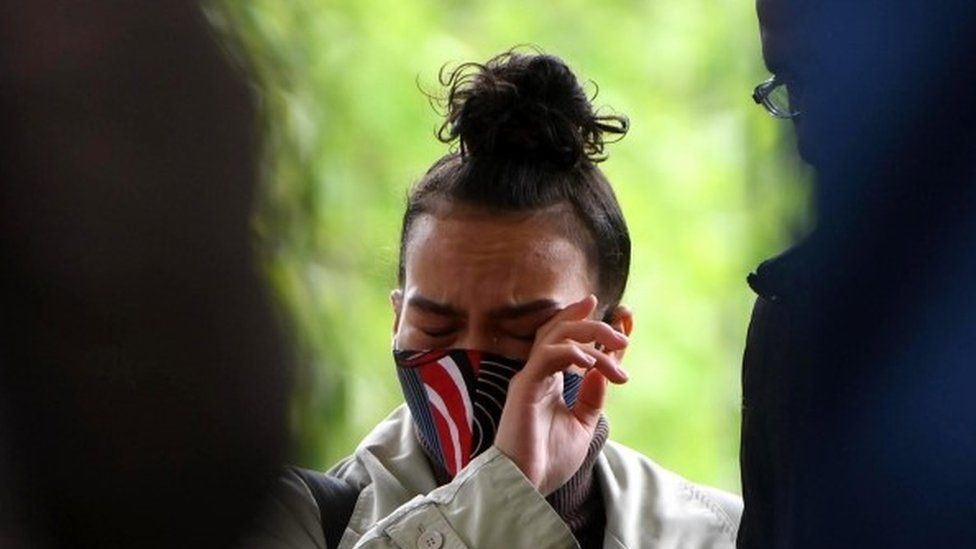 A well wisher wipes her eye as she attends a vigil for Sasha Johnson
