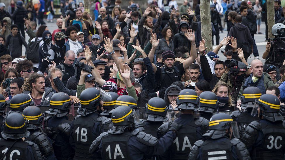 Protesters raise their hands as French Riot Police advance