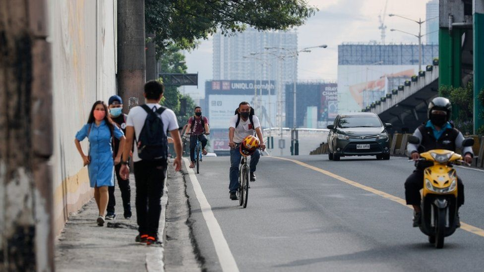 People walk and ride bicycles to work along a highway in Makati, Philippines, 04 August 2020.