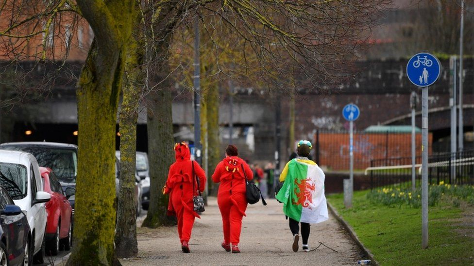 Two women in red dragon fancy dress outfits with a third wearing a Welsh flag as a cape