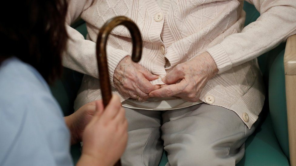 Healthcare worker with elderly woman in care home