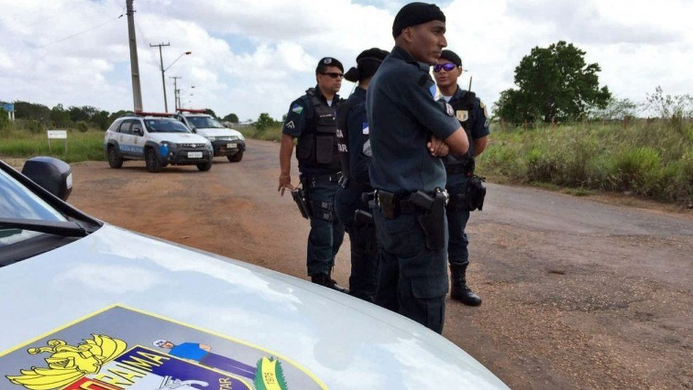 Police stand outside the prison, in the outskirts of the state capital, Boa Vista