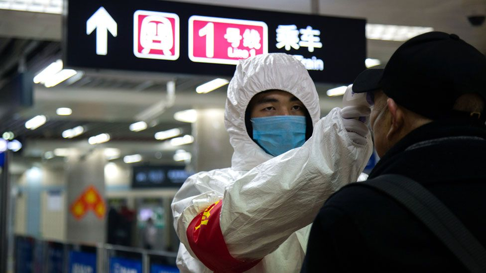 A health worker checks the temperature of a man in Beijing