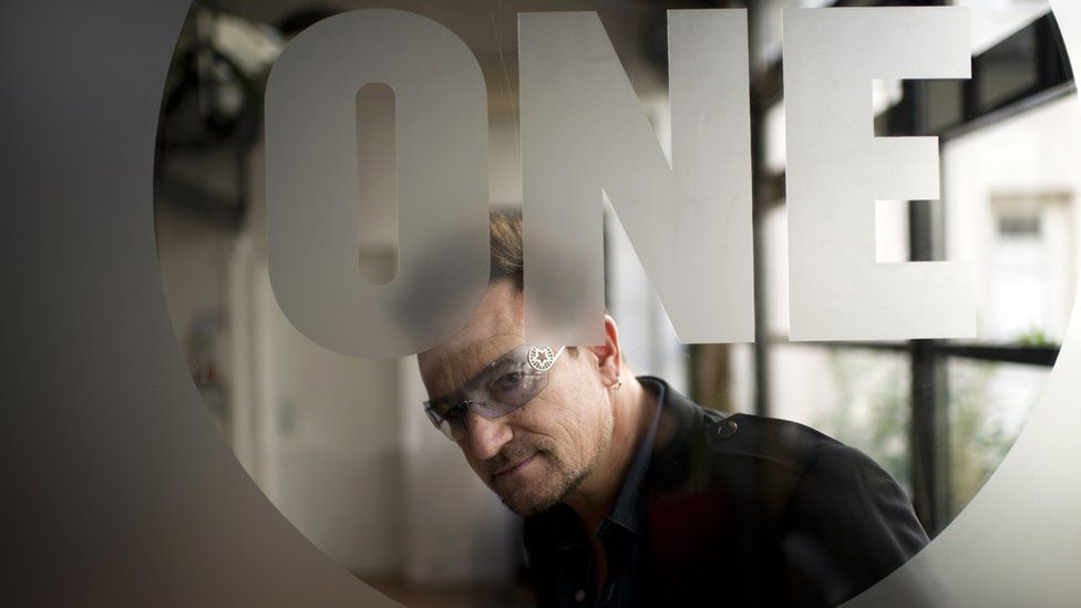 Bono looks through a sheet of glass which is etched with the logo of his charity organisation One