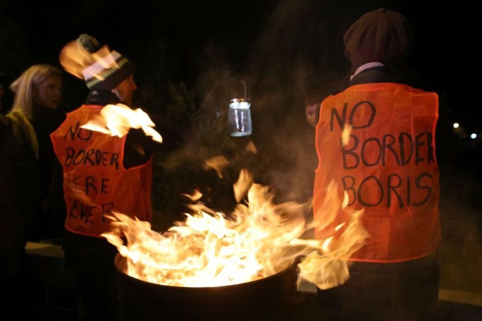 Anti-Brexit protesters standing beside a burning barrel on the Irish border