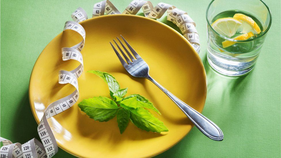 Leaf and measuring tape on a plate with lemon water