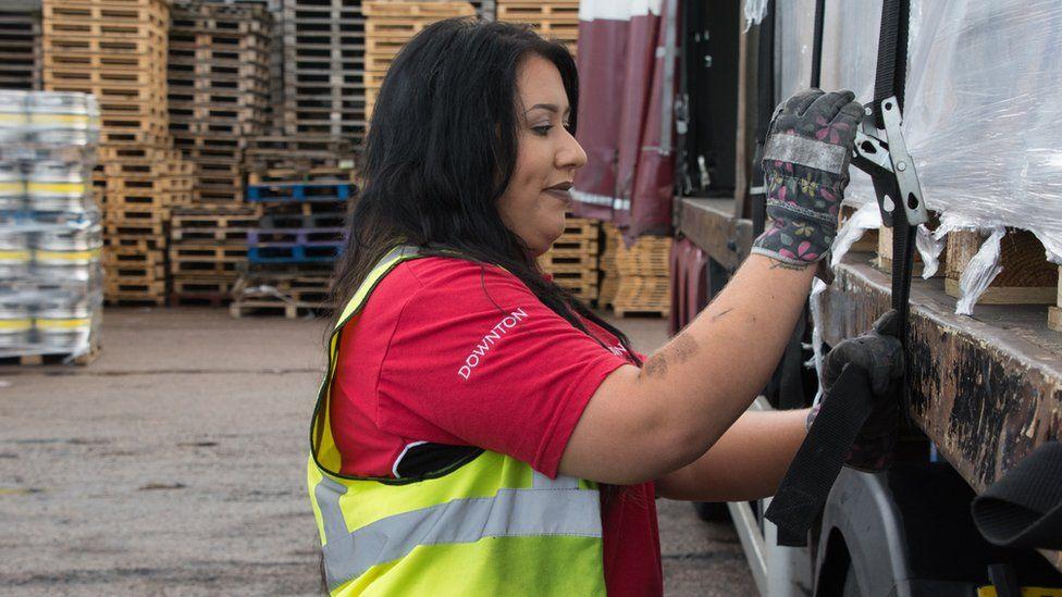 Leonie John tightening straps on a trailer