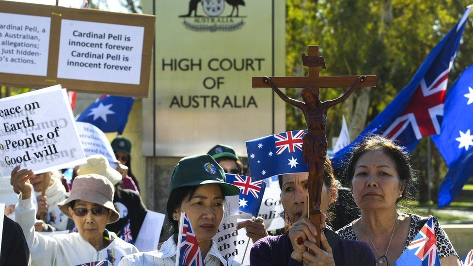 Supporters of George Pell carry crosses and signs outside the High Court of Australia during his appeal hearing