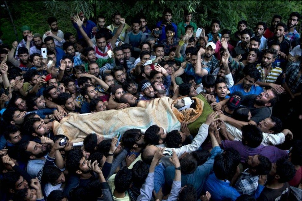 """In this July 9, 2016 file photo, Kashmiri villagers carry the body of Burhan Wani, chief of operations of Indian Kashmir""""s largest rebel group Hizbul Mujahideen, during his funeral procession in Tral, some 38 Kilometers (24 miles) south of Srinagar, Indian controlled Kashmir."""