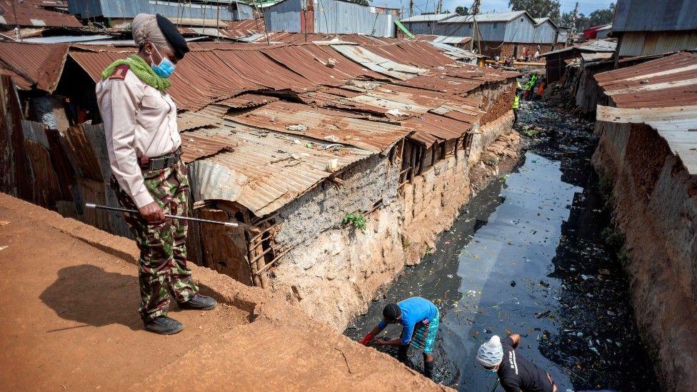 Someone looking at people cleaning an open sewer between corrugated iron houses in Kibera, Nairobi, Kenya