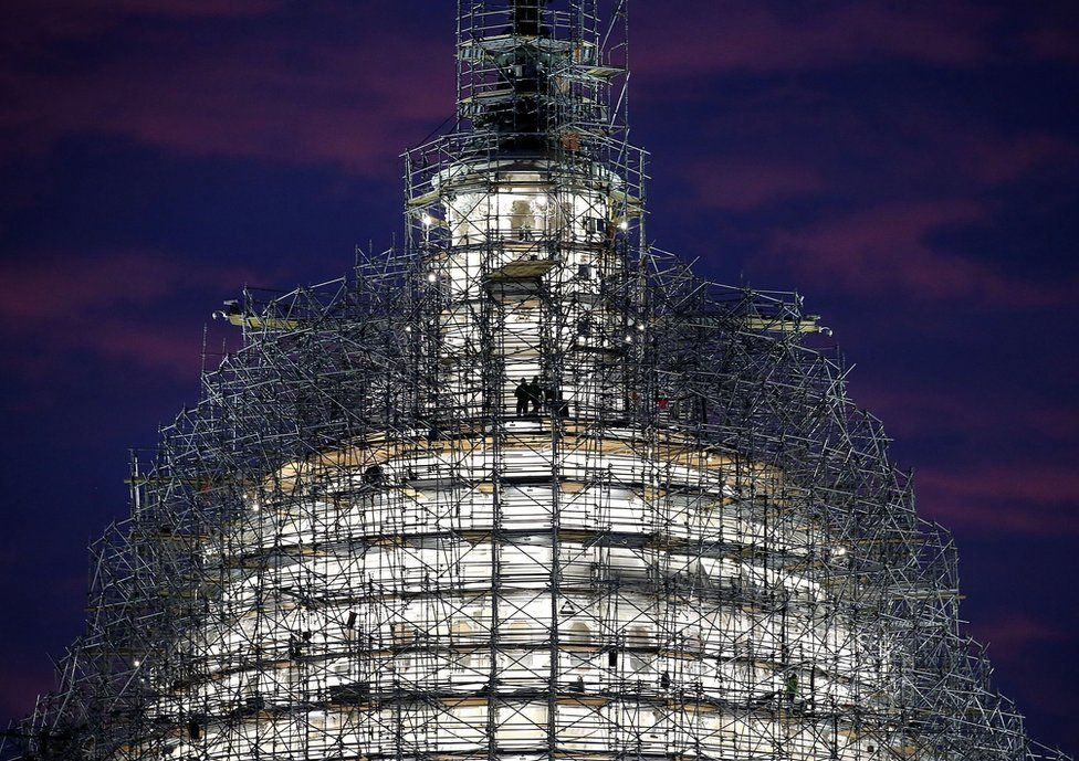 Workers stand on the scaffolding that surrounds the dome of the US Capitol