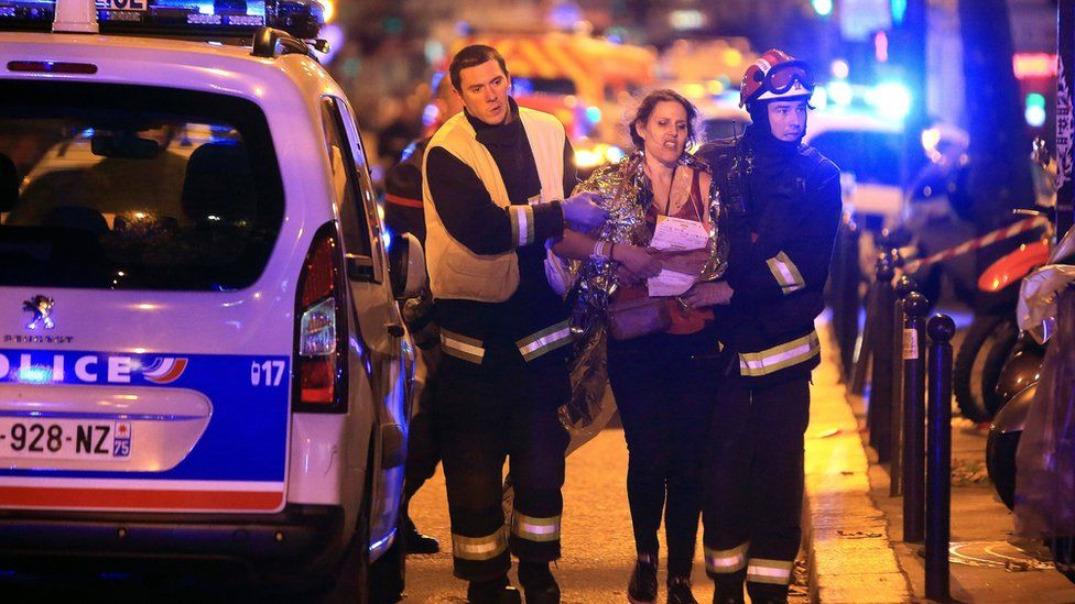 Rescue workers help a woman after a shooting, outside the Bataclan theatre in Paris