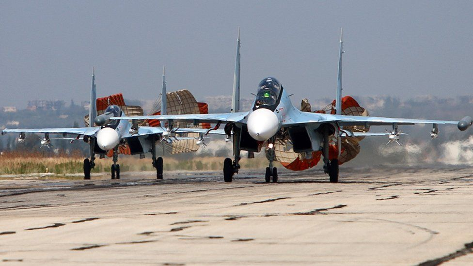 A picture taken on October 3, 2015 shows Russian Sukhoi SU-30 SM jet fighters landing on a runway at the Hmeimim airbase in the Syrian province of Latakia