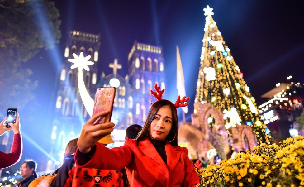 """A woman takes a selfie outside . Joseph""""s cathedral in Hanoi on December 24, 2019."""