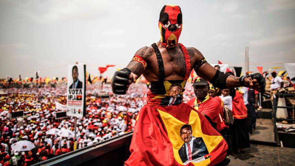A wrestler poses on top of a truck overlooking a crowd attending an electoral meeting by Angolan President and The People's Movement for the Liberation of Angola President Jose Eduardo dos Santos and MPLA presidential Candidate Joao Lourenço