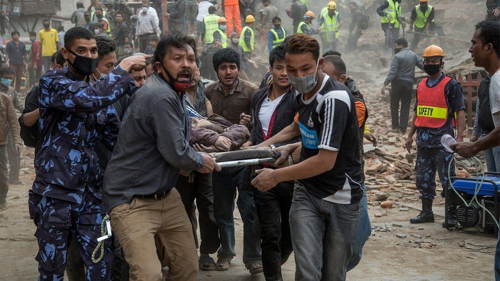 Men carrying a stretcher with rubble in the background