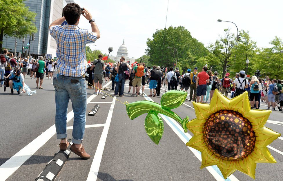 A man with a giant balloon of a sunflower tethered to himself waits for the start of a march by demonstrators down Pennsylvania Avenue