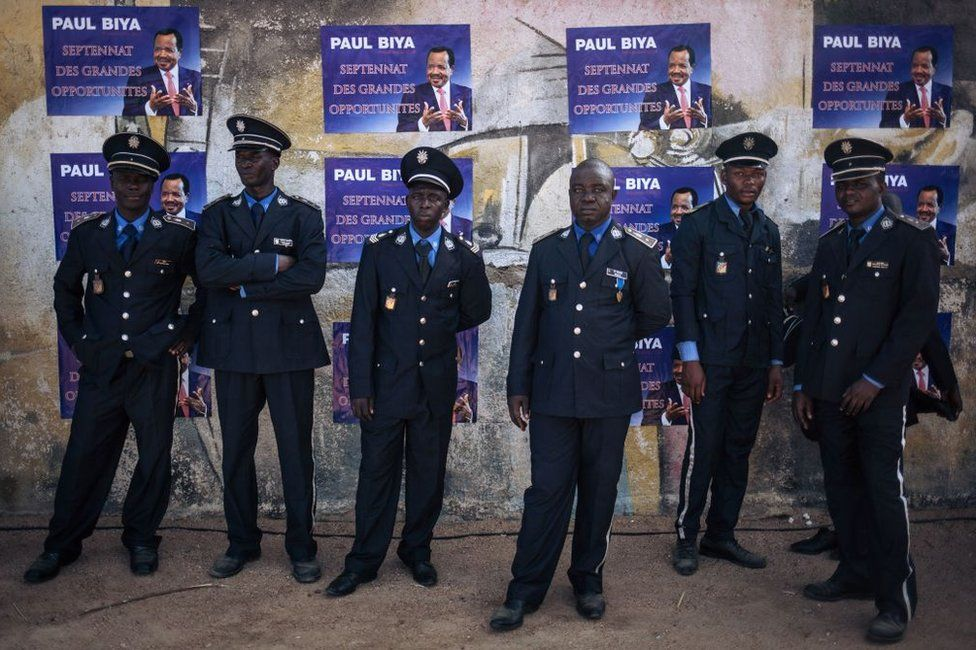 Policemen wait in the shade after Cameroon's president Paul Biya's electoral meeting in Maroua