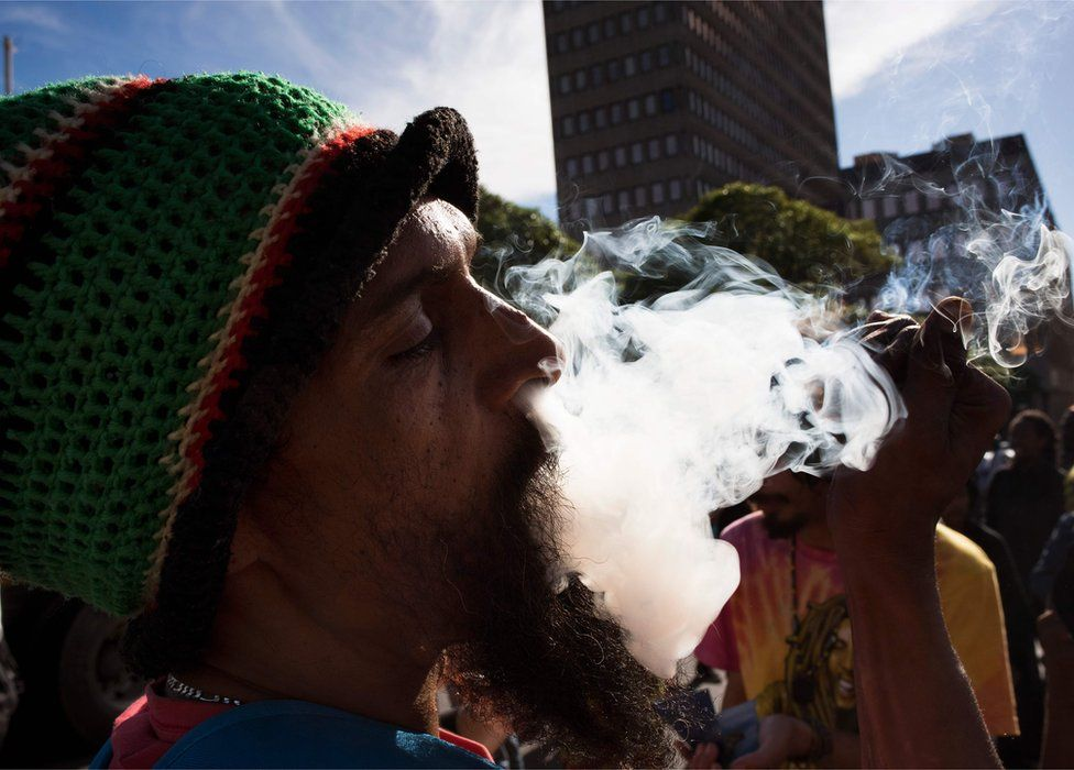 A man smokes marijuana out of a bottle-neck pipe, joining about 1500 people as they protest in front of the parliament in Cape Town, South Africa - 5 May 2018