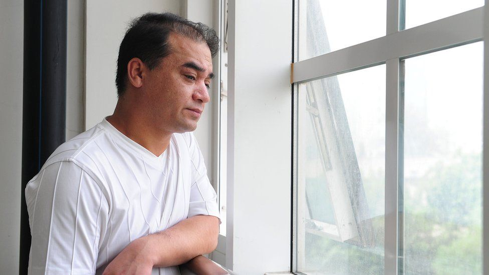 University professor and Uighur activist Ilham Tohti pauses at a window before a classroom lecture in Beijing on 12 June 2010