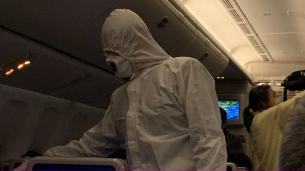飞机上替乘客测量体温的空乘人员