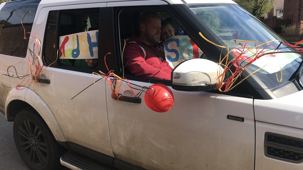 Car decorated with birthday banners and balloons.