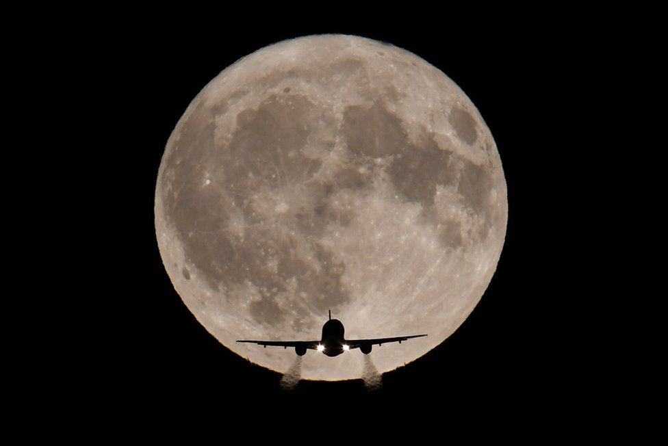 A passenger plane, with a full Harvest moon seen behind, made its final landing approach towards Heathrow Airport in London, Britain, 5 October 2017.