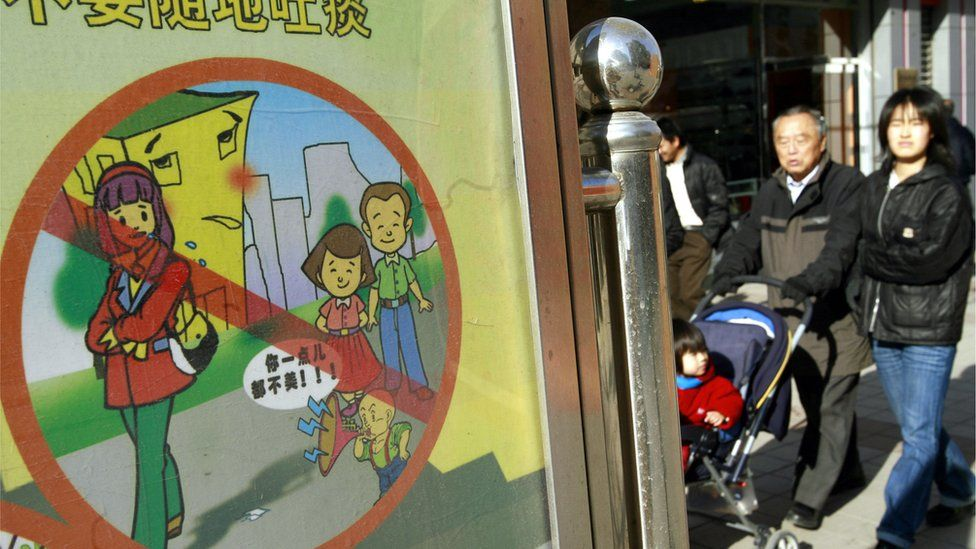 Pedestrians walk past a signboard reading 'please do not spit and others social ills', on display along a street in Beijing, 17 November 2007, ahead of the 2008 Olympics.