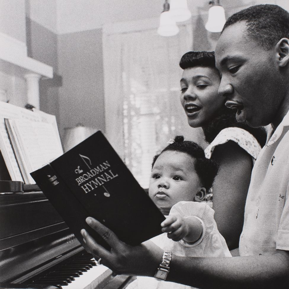 Coretta Scott King, Martin Luther King and one of their children sing a hymn at the piano - Montgomery, 1956